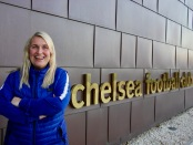 Emma Hayes posing by the Chelsea FC sign