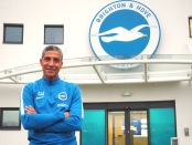 Chris Hughton posing outside the Brighton & Hove Albion offices