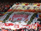 Large banner displaying the Liverpool FC club crest being held by fans during a game
