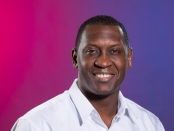 Photo of Emile Heskey in front of a pink and purple gradient background