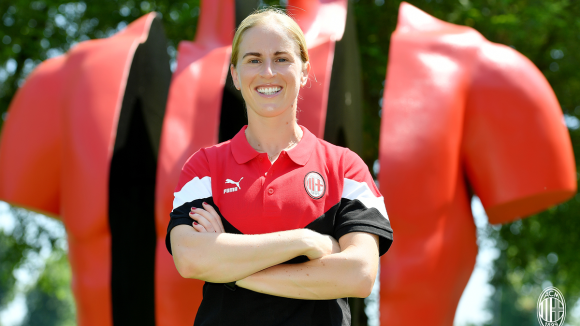 Natasha Dowie wearing a red and black AC Milan polo shirt standing in front of a statue at San Siro Stadium